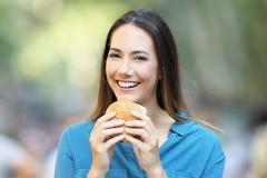 Mujer que sostiene una hamburguesa que mira la cámara Fotografía de archivo