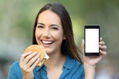 Mujer que sostiene una hamburguesa que muestra una pantalla del teléfono Imágenes de archivo libres de regalías