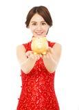 Mujer que sostiene una hucha de oro Año Nuevo chino feliz Imagen de archivo libre de regalías