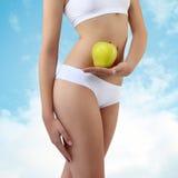 Mujer que sostiene una manzana con las manos cerca del vientre, en fondo del cielo Fotos de archivo