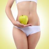 Mujer que sostiene una manzana con sus manos cerca del vientre Foto de archivo