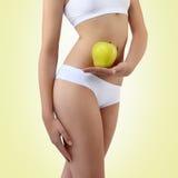 Mujer que sostiene una manzana con sus manos cerca del vientre Imagen de archivo