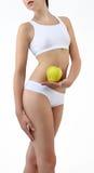 Mujer que sostiene una manzana con sus manos cerca del vientre Imagenes de archivo