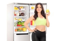 Mujer que sostiene una manzana delante de un refrigerador Imágenes de archivo libres de regalías