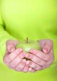 Mujer que sostiene una manzana verde fresca entera fotografía de archivo