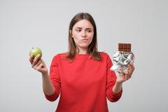 Mujer que sostiene una manzana verde y un chocolate Fotografía de archivo libre de regalías