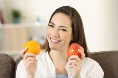 Mujer que sostiene una manzana y en una cámara de mirada anaranjada Foto de archivo