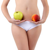Mujer que sostiene una manzana y un melocotón con sus manos cerca del vientre Imagen de archivo