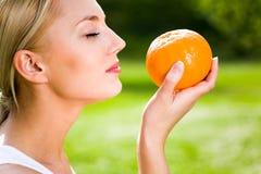 Mujer que sostiene una naranja imagen de archivo libre de regalías