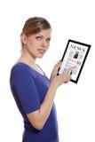Mujer que sostiene una PC del touchpad, leyendo un periódico Foto de archivo libre de regalías