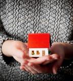 Mujer que sostiene una pequeña nueva casa en sus manos Imagen de archivo