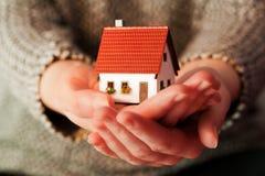 Mujer que sostiene una pequeña nueva casa en sus manos Imágenes de archivo libres de regalías