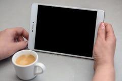 Mujer que sostiene una tableta con una taza de café Fotografía de archivo