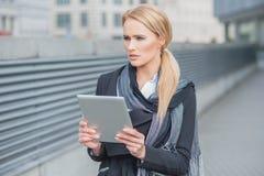 Mujer que sostiene una tableta que se coloca de pensamiento Imagenes de archivo