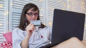 Mujer que sostiene una tarjeta de crédito para las compras en línea almacen de metraje de vídeo
