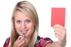 Mujer que sostiene una tarjeta roja Imagen de archivo libre de regalías