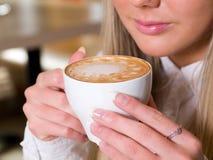 Mujer que sostiene una taza de bebida caliente Imágenes de archivo libres de regalías