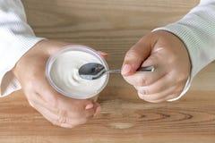 Mujer que sostiene una taza de yogur y de cuchara disponibles en la tabla Yogur hecho de la leche fermentada por las bacterias añ imagen de archivo