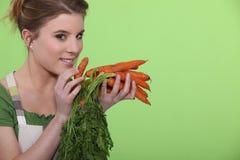 Mujer que sostiene zanahorias Foto de archivo libre de regalías