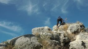 Mujer que sube una montaña y que celebra almacen de metraje de vídeo