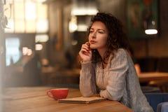 Mujer que sueña con la taza de café en café Imágenes de archivo libres de regalías