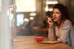 Mujer que sueña con la taza de café en café Foto de archivo libre de regalías