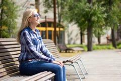 Mujer que sueña despierto atractiva joven que se sienta en parque Fotos de archivo libres de regalías