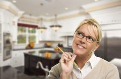 Mujer que sueña despierto con el lápiz dentro de la cocina de encargo hermosa imagen de archivo libre de regalías