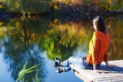 Mujer que sueña por el lago en parque del otoño Imágenes de archivo libres de regalías