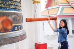 Mujer que suena una campana en un templo budista Fotografía de archivo