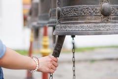 Mujer que suena una campana en un templo budista Foto de archivo