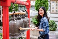Mujer que suena una campana en un templo budista Foto de archivo libre de regalías