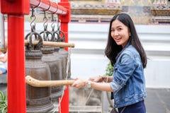 Mujer que suena una campana en un templo budista Imágenes de archivo libres de regalías