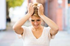 Mujer que sufre de dolor de cabeza al aire libre Foto de archivo