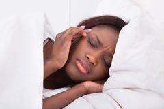 Mujer que sufre de dolor de cabeza en cama en casa Imagen de archivo libre de regalías
