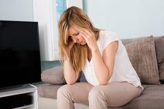 Mujer que sufre de dolor de cabeza en casa Foto de archivo libre de regalías