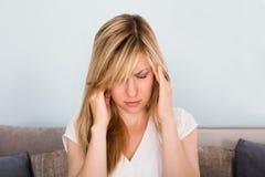 Mujer que sufre de dolor de cabeza en casa Fotos de archivo