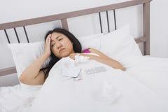 Mujer que sufre de dolor de cabeza y de la mentira fría en cama Foto de archivo