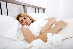 Mujer que sufre de dolor del abdomen en cama Imagen de archivo