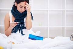 Mujer que sufre de la mentira fría en cama con el tejido Fotografía de archivo libre de regalías