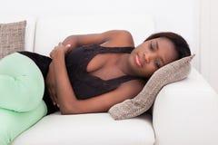 Mujer que sufre del dolor de estómago en casa Imagenes de archivo