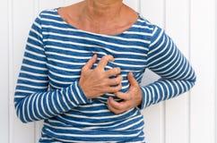 Mujer que sufre dolores de pecho severos Foto de archivo libre de regalías