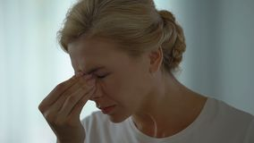 Mujer que sufre la jaqueca terrible, quitando las lentes, hipertensión, tensión almacen de metraje de vídeo