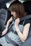 Mujer que sujeta su cinturón de seguridad Imagen de archivo