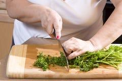 Mujer que taja el perejil en cocina Fotos de archivo