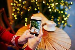 Mujer que tarda a foto PF su taza y regalo de Navidad de café fotos de archivo libres de regalías