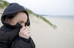 Mujer que tiembla en la playa Imagenes de archivo