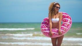 Mujer que tiene baile de la diversión y de la sonrisa con el buñuelo rosado muchacha en gafas de sol que llevan del bicini en la  metrajes