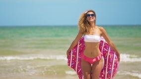 Mujer que tiene baile de la diversión y de la sonrisa con el buñuelo rosado Muchacha en gafas de sol que llevan del bikini en la  metrajes