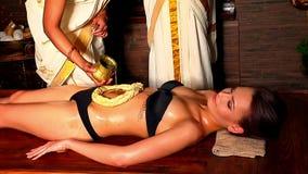 Mujer que tiene balneario exótico del tratamiento del estómago indio usando el aceite de colada de la pasta almacen de metraje de vídeo